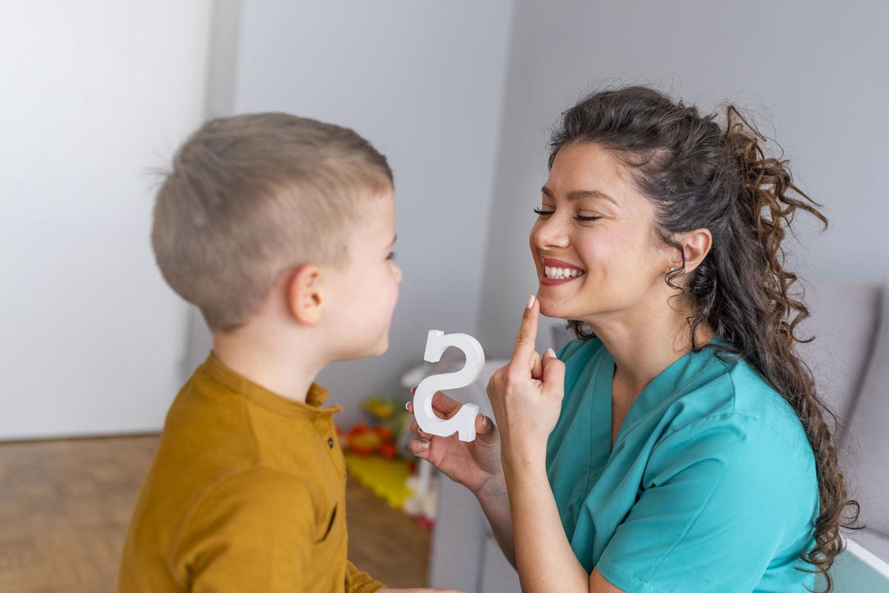 orthophoniste lors d'une seance avec un petit garçon