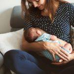 Jeune maman allaite son bébé, lui tenant dans ses bras