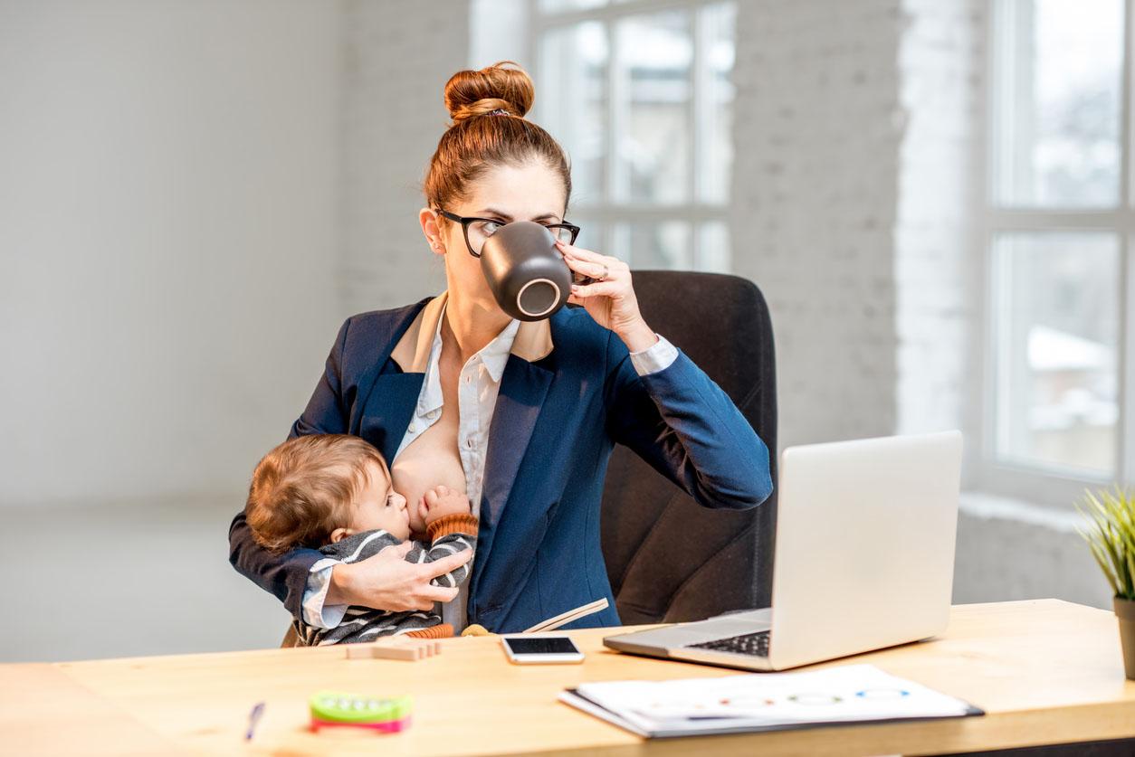Femme d'affaires travaillant au bureau donnant le sein à son bébé