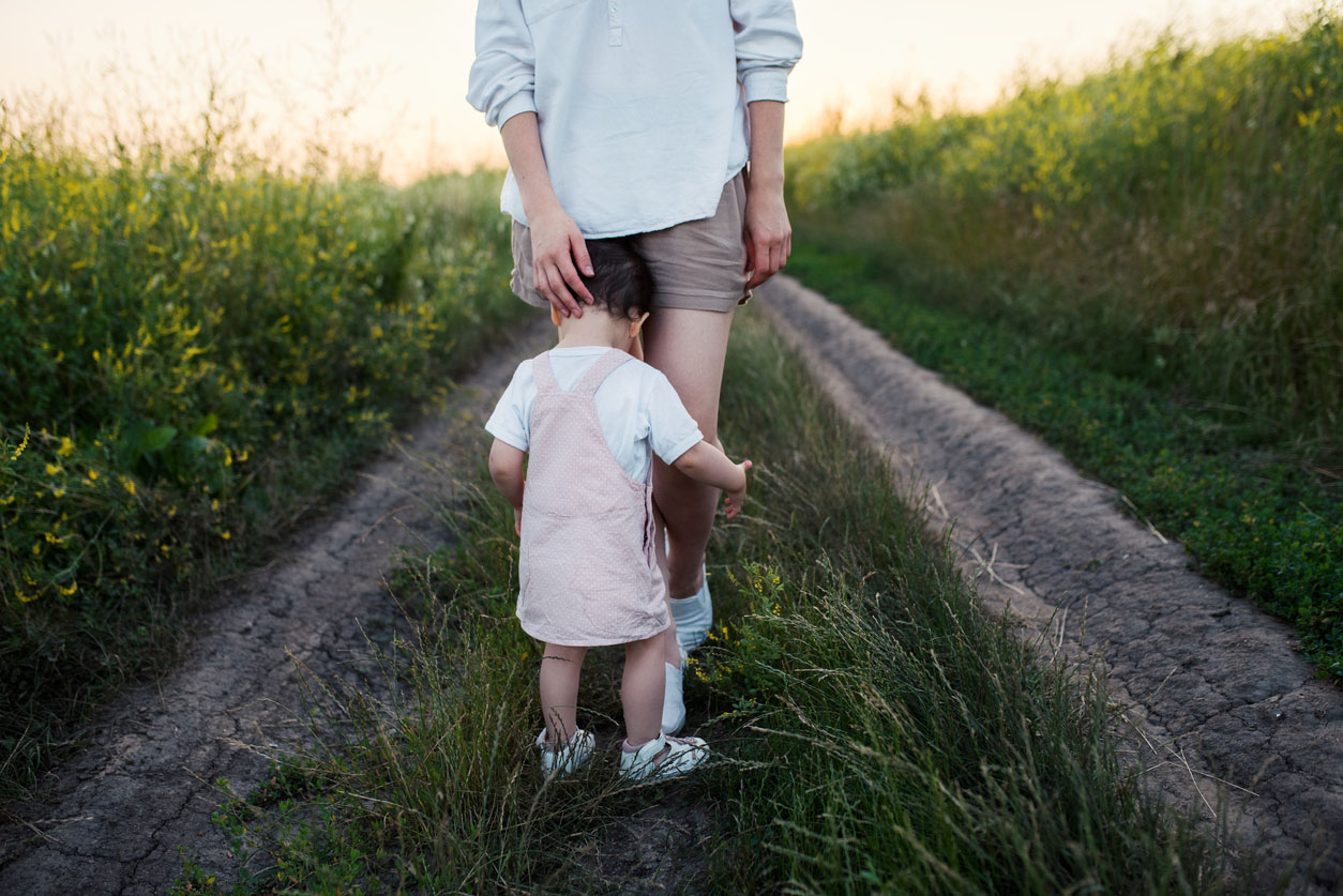 enfant qui pleure dans les jambes de sa maman