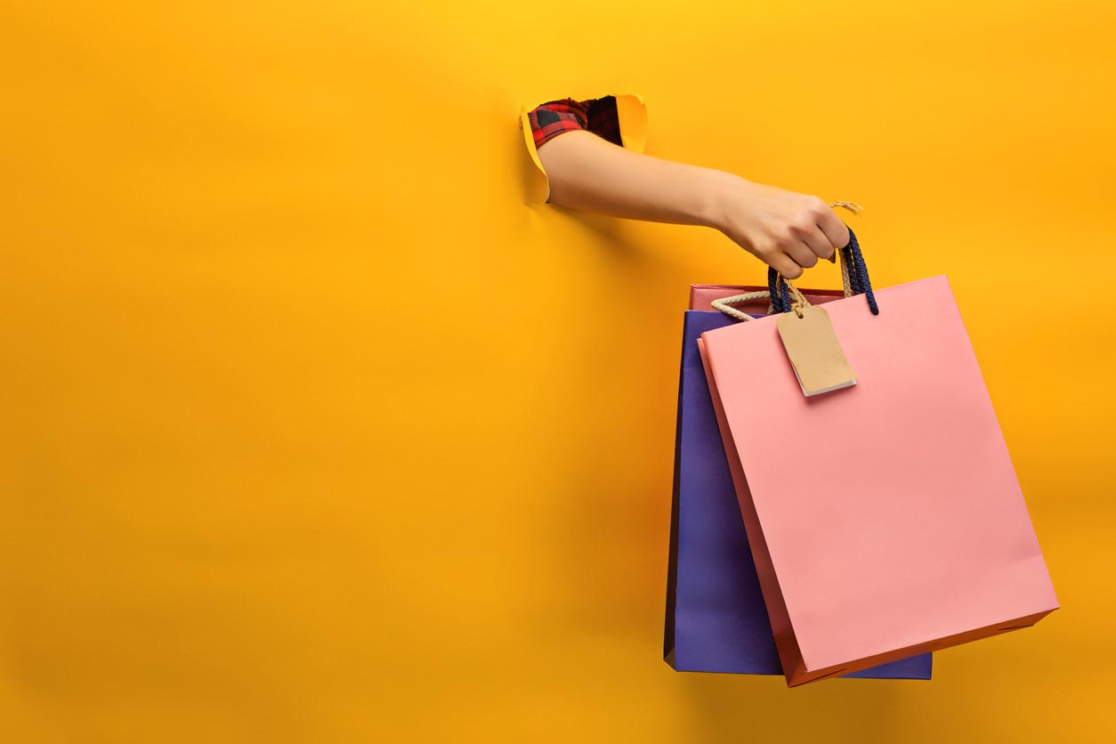 Female Hand Holding Bright Shopping Bags