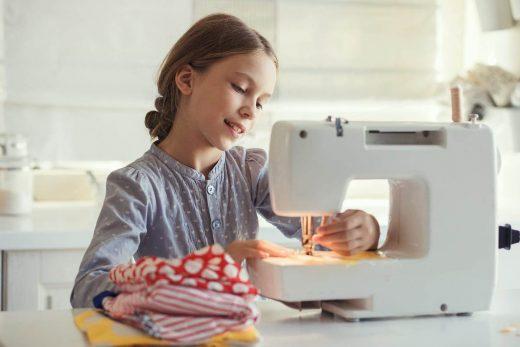 Petite Fille Qui Utilise Une Machine à Coudre