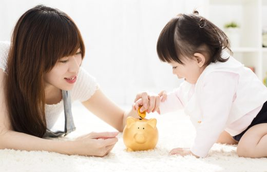 Mother And Daughter Putting Coins Into Piggy Bank
